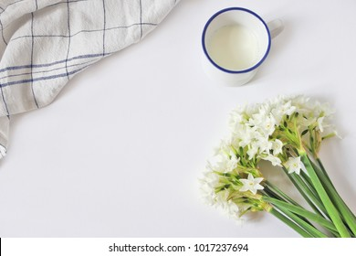 Breakfast scene with mug of milk, tea towel and bouquet of narcissus, daffodil flowers on white table background. Spring composition, Easter concept. Flat lay, top  view. Styled stock image.