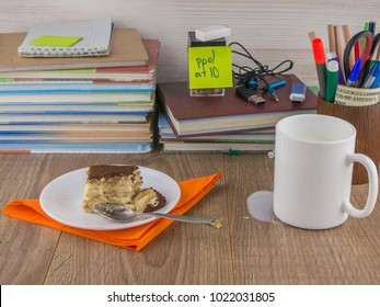 Breakfast at schoolboy-dirty: a mug of milk, a piece of cake and a teaspoon on an orange napkin on a plate, milk spilled on the desktop