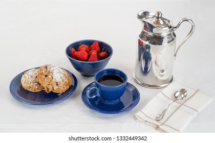 Breakfast of Scones on a Dark Blue Plate and Bowl of Fresh Strawberries with Coffee and a Silver Hotel Room Service Carafe on a White Linen Tablecloth with a Napkin and Spoon.