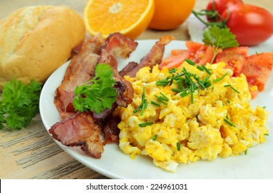 Breakfast with scrambled eggs with chive, bacon and fresh tomatoes