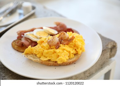 breakfast with scrambled eggs, fried potatoes bacon and shrimp