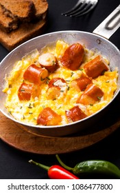 Breakfast of scrambled eggs and sausages in a pan on black background.