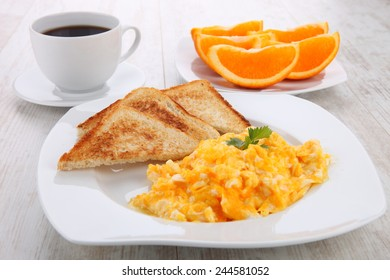 breakfast with scrambled eggs, toasts, juice