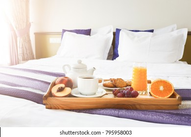 Breakfast served in bed on wooden tray with tea, juice, cookies and fruit. Hotel room service, relax concept, copy space