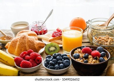 Breakfast served with coffee, orange juice, toasts, croissants, cereals, milk, nuts and fruits. Balanced diet. healthy food. close up