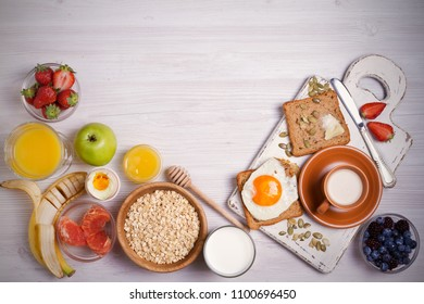 Breakfast served with coffee, orange juice, oat cereal, milk, fruits, eggs and toast. Balanced diet. Morning sweet and savory meal, food background. overhead, horizontal