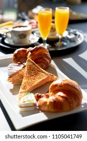 Breakfast served with coffee, orange juice, croissant, toast bread and jam, selective focus. Sunny weather, no people
