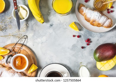 Breakfast served with coffee, orange juice, croissants and fruits on concrete background