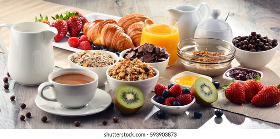 Photo of Breakfast served with coffee, orange juice, croissants, cereals and fruits. Balanced diet.