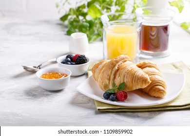 Breakfast served with croissants, coffee, orange juice and berries.