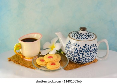 Breakfast is served with tea, in glass and in the pot. There are cookies in the plate and the flowers are placed on a white table. The back wall is a patterned blue cement wall.