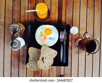 Breakfast set, fried eggs, toast, orange juice, milk and tea.