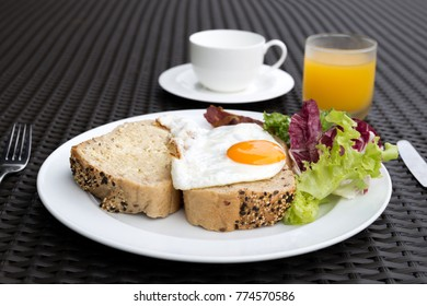 Breakfast set with fried eggs,vegetable,bread,coffee and orange juice in the morning