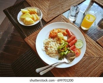 Breakfast set including Asian style food, fresh fruit and juice.