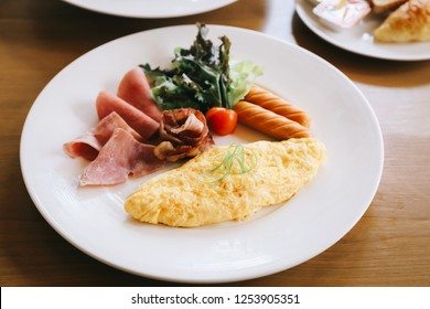 Breakfast set Omelette with sausage bacon and salad on wood background