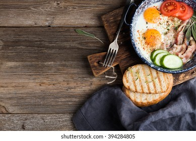 Breakfast set. Pan of fried eggs with bacon, fresh tomato, cucumber, sage and bread on rustic serving board over wooden background, top view, copy space