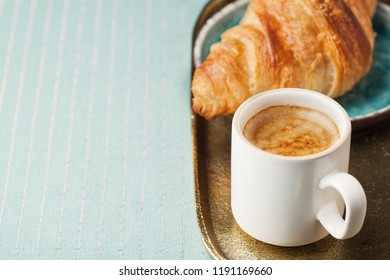 Breakfast setting with cup of black coffee and croissant