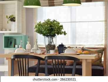 Breakfast setup on wooden table with nice vase and modern chair