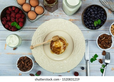 Breakfast. A short stack of pancakes on rustic wood table with organic eggs, sour cream, honey, milk, raspberry, blueberry, almonds, pecans