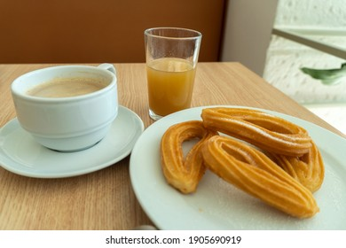 Breakfast in Spain with coffee orange juice and churros