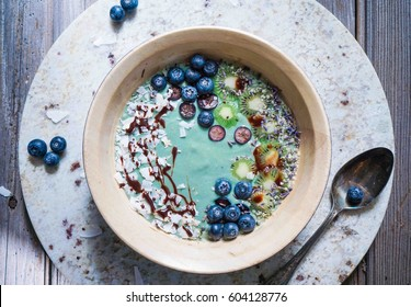 Breakfast spirulina coconut smoothie bowl topped with coconut flakes and berries on wood background, top view, toning. Close up.