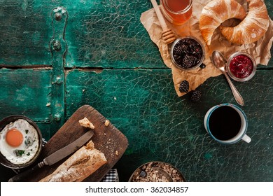 Breakfast spread with coffee, bread, fresh croissants, fried egg, honey and preserves on an old rustic green wooden table, overhead view with copyspace