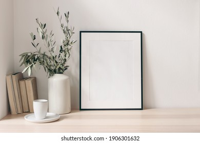 Breakfast still life. Cup of coffee, books and empty picture frame mockup on wooden desk, table. Vase with olive branches. Elegant working space, home office concept. Scandinavian interior design. - Shutterstock ID 1906301632