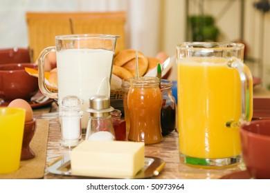 Breakfast still life with orange juice, focus on marmalade jar