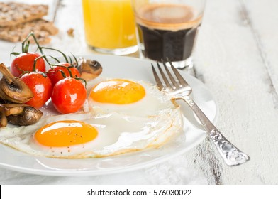 Breakfast of sunny side up eggs with mushrooms and tomatoes, coffee and orange juice on white wooden background