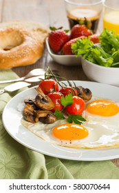 Breakfast of sunny side up eggs with mushrooms and tomatoes, coffee and orange juice on wooden background