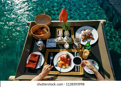 Breakfast in swimming pool, floating breakfast in tropical resort. Girl relaxing in the pool drinking coffee and eating fruit plate by the hotel pool. Exotic summer diet. Tropical beach lifestyle