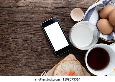 breakfast table with blank screen on smartphone for text, top view kitchen table.