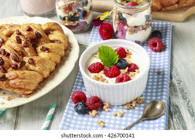 Breakfast table: bowl of yogurt with muesli and fresh fruits: raspberries and blueberries, glass jars with fruits and whipped cream and braided danish bun made of puff pastry.