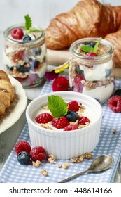 Breakfast table: bowl of yogurt with muesli and fresh fruits: raspberries and blueberries, glass jars with fruits and whipped cream.