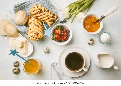 Breakfast table. Coffee, eggs, milk, buns, juice and jam. Blue background, top view, food flat lay.