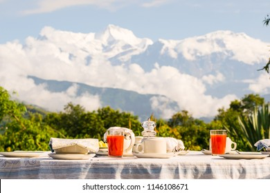 Breakfast table with coffee, tea and watermelon juice dressed in front of the Annapurna mountain range, Himalayas, Nepal.