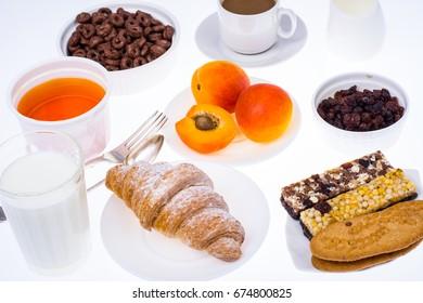 Breakfast table with croissant, muesli, milk, honey and fruits. Studio Photo