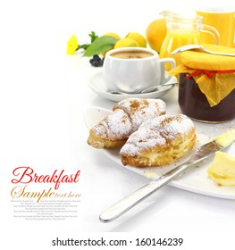 Breakfast table with croissants and beverages