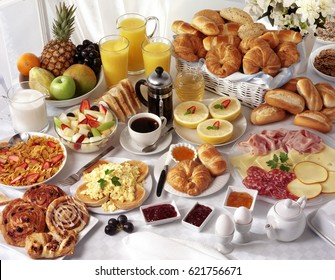 BREAKFAST TABLE FILLED WITH ASSORTED FOODS,SAVOURY,SWEET,PASTRIES,HOT AND COLD DRINKS