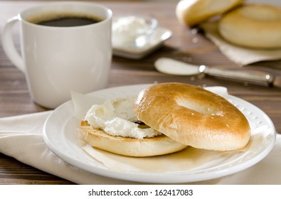 Breakfast table with a fresh cup of coffee and a toasted bagel with cream cheese.
