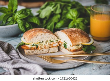 Breakfast table with fresh fried fish sandwich with tartare sauce, lemon and arugula cut in halves, fresh greens and glass of orange juice. Healthy easy breakfast ideas