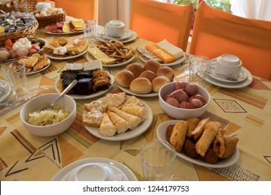 A breakfast table full of food in Nova Petropolis, Brazil, Serra Gaúcha. A typical meal called Cafe Colonial, showing some plates with different kinds of food