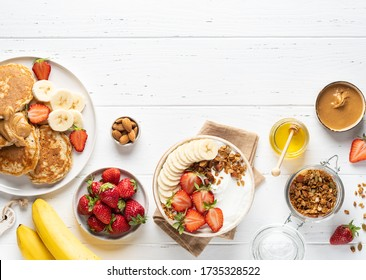Breakfast table. Granola, honey and nuts, yogurt, banana pancakes , peanut butter and fresh strawberry. Healthy and tasty family morning meal concept. White wooden background. Copy space. Top view.