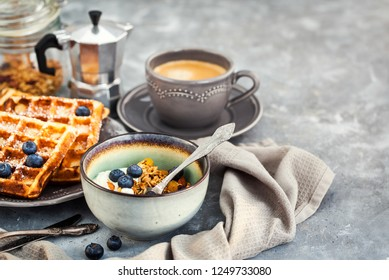 Breakfast table with granola and yogurt, fresh homemade belgian waffles and cup of hot black coffee