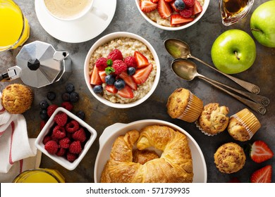 Breakfast table with oatmeal porridge, croissants, fresh fruit and muffins overhead shot