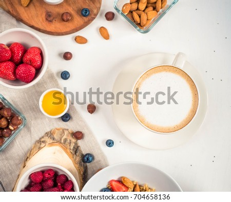 Breakfast table with oatmeal porridge, croissants, fresh fruit overhead shot