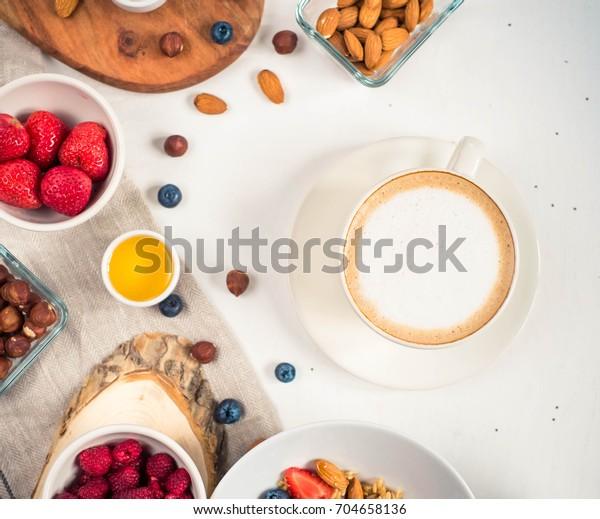 Breakfast table with oatmeal porridge, croissants, fresh fruit overhead shot