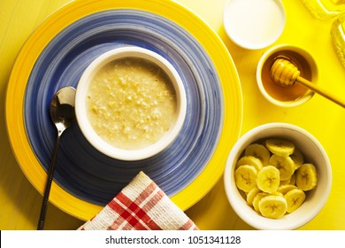 A breakfast table of organic hot porridge and banana with honey