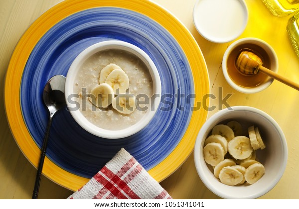 A breakfast table of organic hot porridge and banana with honey. Bright and cheerful place setting