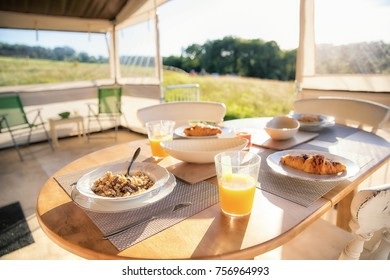 Breakfast table set and laid with bowls of cereal and a glass of orange fruit juice. The front of the glamping tent is open with fields in sunshine as the view.